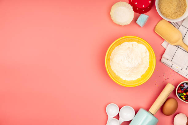 Baking or cooking ingredients on pink background, flat lay