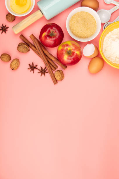 Baking or cooking ingredients on pink background, flat lay stock photo