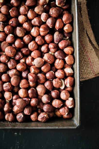 Baking Pan Full of Shelled Hazelnuts on Black stock photo