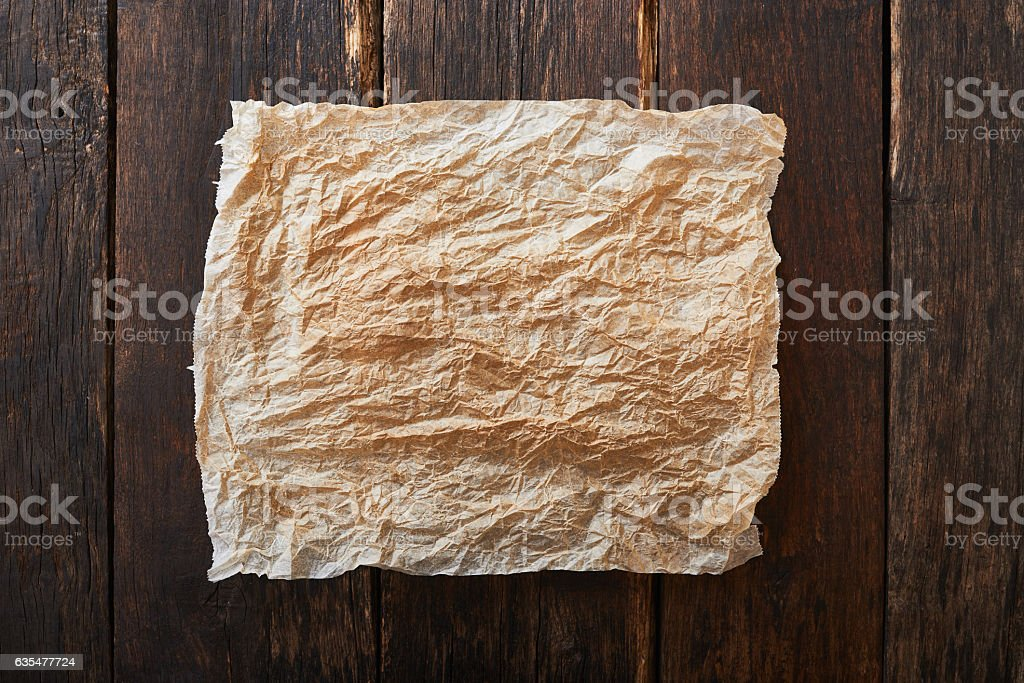 Baking paper on vintage wooden table - background for text stock photo