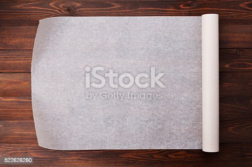 istock Baking paper on wooden kitchen table for menu or recipes 522626260