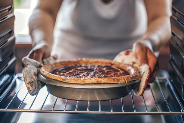 Baking Pecan Pie in The Oven for Holidays Baking Pecan Pie in The Oven for Holidays oven stock pictures, royalty-free photos & images