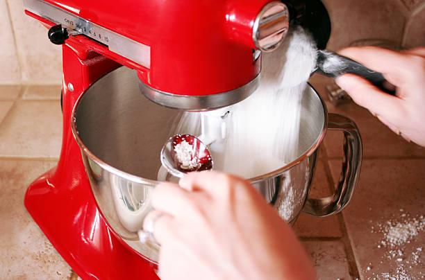 Baking A woman pours flour into a mixer electric mixer stock pictures, royalty-free photos & images