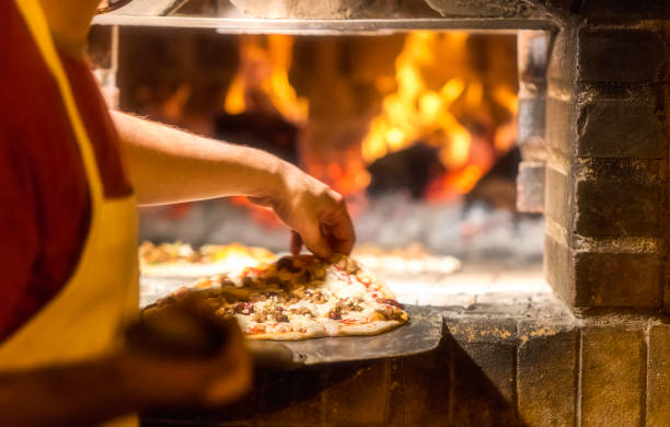 Baking Pizza in a Wood fire Brick oven Cook cooking Pizza in a wood fire Brick oven at a pizzeria log fire stock pictures, royalty-free photos & images