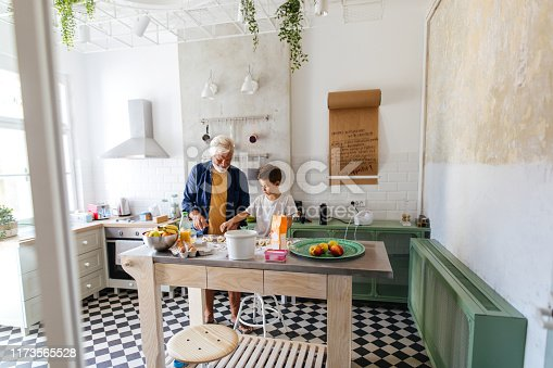 Little boy and his grandfather baking rolls in their kitchen