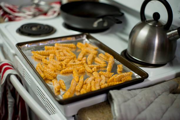 en plåt fodrad med folie, täckt av frysta pommes frites - bakplåt bildbanksfoton och bilder
