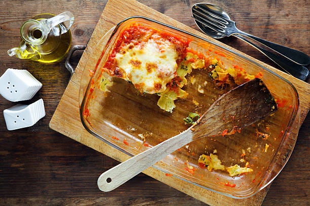 baking sheet of glass with the remains of lasagna baking sheet of glass with the remains of lasagna leftovers stock pictures, royalty-free photos & images