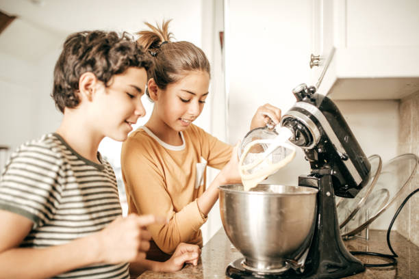 Baking siblings Baking siblings electric mixer stock pictures, royalty-free photos & images