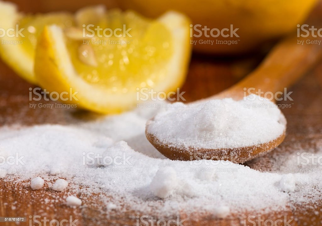 baking soda (sodium bicarbonate) in a wooden spoon and lemon stock photo