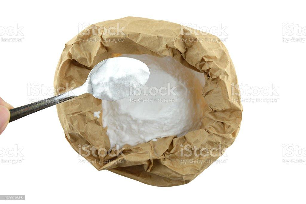 Bicarbonate de soude en contient en sac en papier brun, isoler arrière-plan - Photo