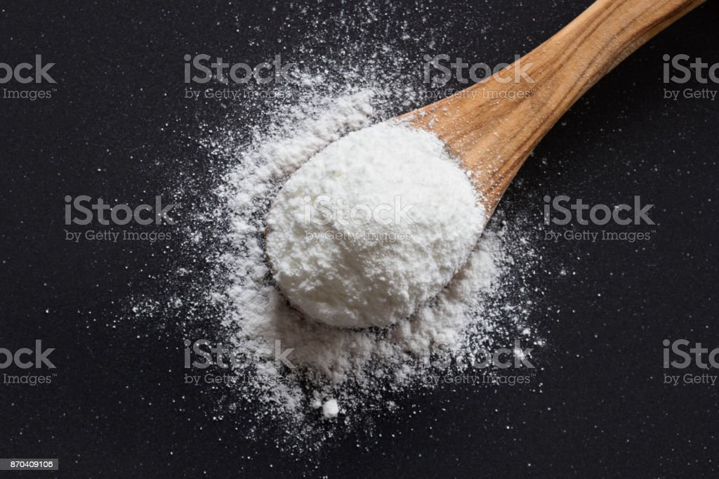 Baking soda on a wooden spoon stock photo
