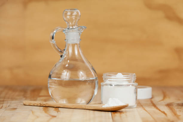 baking soda - sodium bicarbonate and vinegar, on wooden background baking soda - sodium bicarbonate and vinegar, on wooden background vinegar stock pictures, royalty-free photos & images