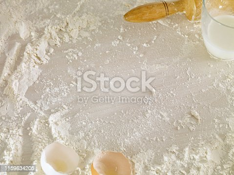 Looking down a table with flour, eggs and rolling pin