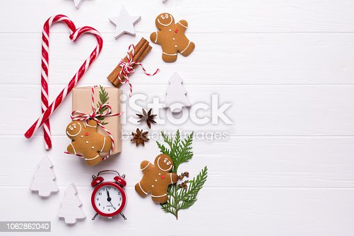 istock Baking time. Preparation for the holidays. Christmas or New Year background with cookies, ribbon, candy cane, Christmas ornaments, gift box, pine cones and fir branches red alarm clock 1062862040