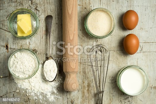 Selection of Baking ingredients shot overhead Flat lay on a distressed wooden background. Includes butter, flour, yeast, sugar, eggs, milk, rolling pin and whisk.