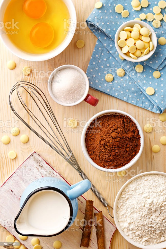 Baking utensils and ingredients. Egg yolk, cocoa, milk, flour, whisker, spoons, cinnamon, bowl, sweet decoration elements. Top view. Flat lay stock photo