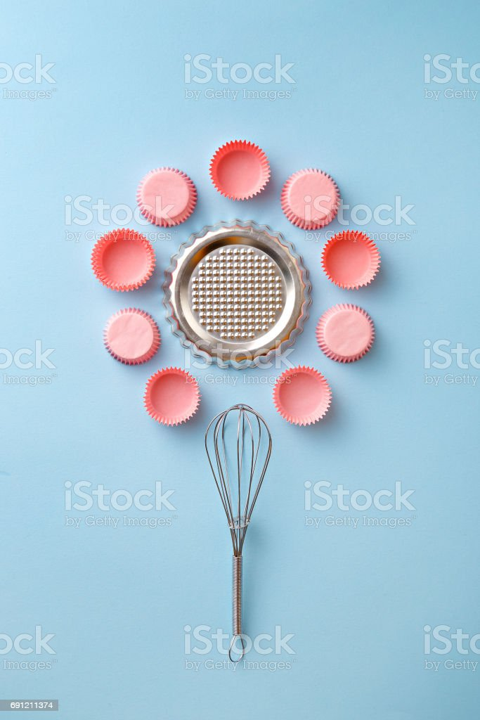 Baking utensils. Whisker, cupcake paper cups, mold. Top view. Flat lay stock photo