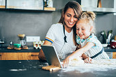 Mother and daughter using digital tablet while baking in the kitchen