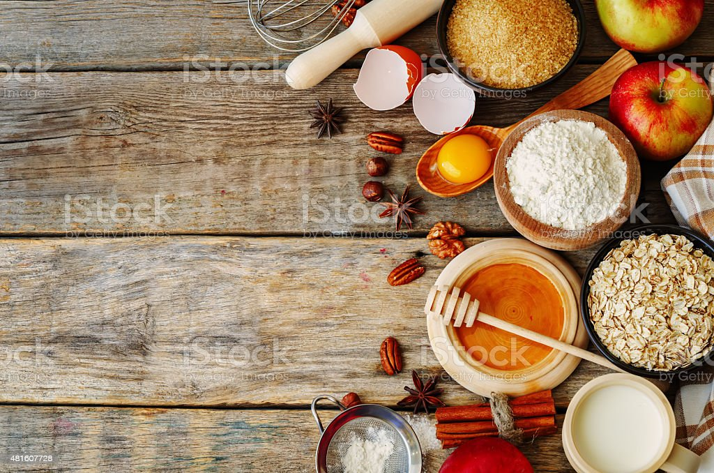 baking wood background with apples, nuts, honey, flour and butter stock photo