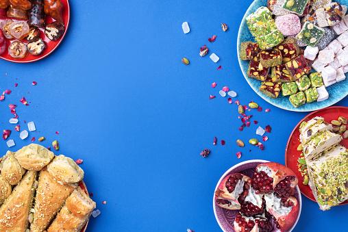 istock Baklava, halva, rahat lokum, sherbet, nuts, pistachios, dates, raisins, dried apricots, churchkhela. Assorted traditional eastern desserts, arabian sweets, turkish delight. Top view. Flat lay 1271667953