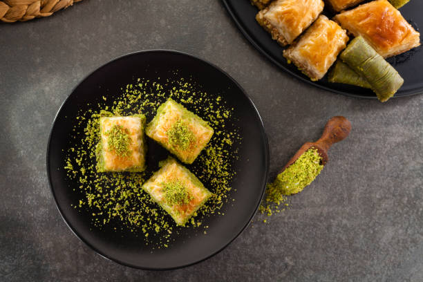 Baklava Baklava on black dish. arabic style stock pictures, royalty-free photos & images