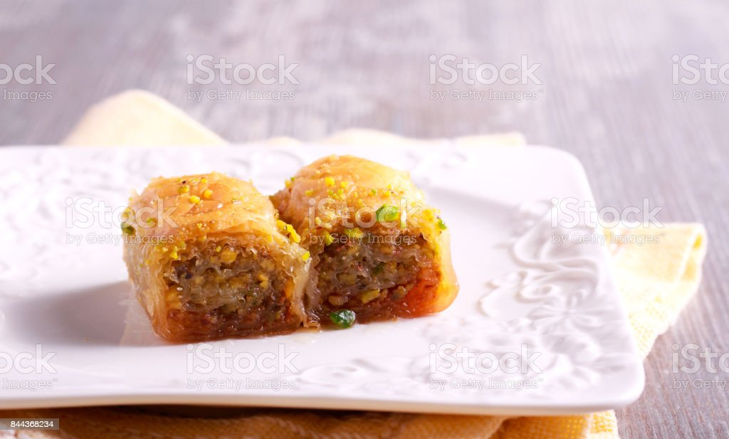 Baklava with pistachios and honey on plate stock photo