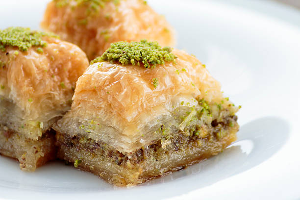 baklava with pistachios and walnuts on white plate - baklava stockfoto's en -beelden