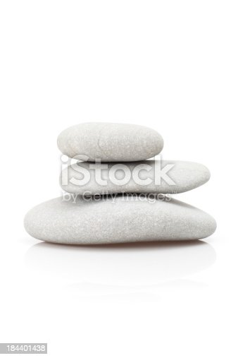 Pile of pebble stones on a white reflective surface. Ideal image for relaxation and zen like designs.