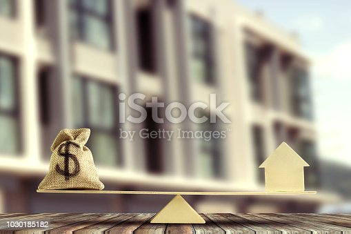 istock Balance home and money concept : us dollar moneybag and home model put on scales on wood table and blurred real estate as background. Savings, investment, loan for plan in the future. 1030185182