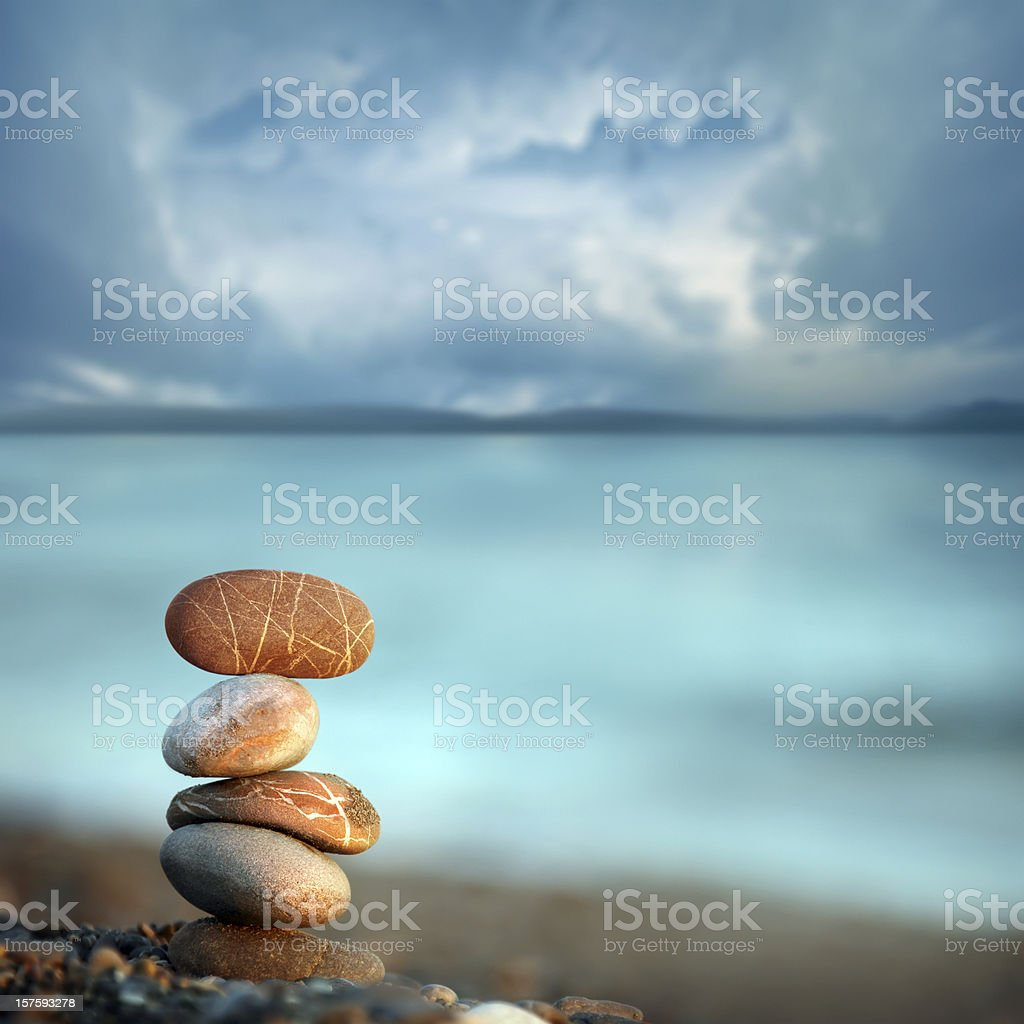 balance in peace morning time pile of pebble stones on beach over cloudy sky and sea. Arrangement Stock Photo