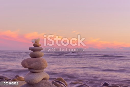 Pyramid of stones of light color against the background of the sea and the sunset sky. Balance of round pebbles against the backdrop of a beautiful sunset.