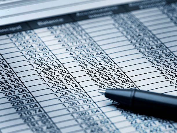 Balance Sheet Close up of paper with numbers and a pen with a blue hue accounting ledger stock pictures, royalty-free photos & images