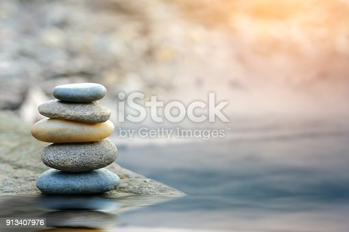 istock Balance stone with spa on river coast 913407976
