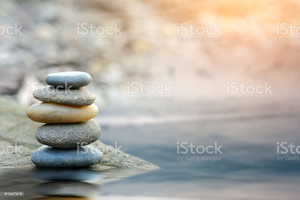 Balance stone with spa on river coast stock photo