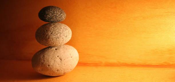Balance stones stacked to pyramid in orange background - foto stock