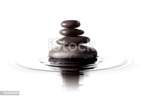 Close up photograph of stacked black massage stones in water. ProPhoto color space.