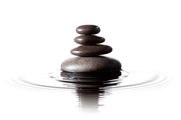 Balanced black stones in water - Feng Shui Massage Lastone Close up photograph of stacked black massage stones in water. ProPhoto color space. buddhism stock pictures, royalty-free photos & images