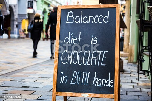 Close up image depicting a street sign outdoors with the humorous caption written in chalk, 'a balanced diet is chocolate in both hands'. Beyond the sign, people and tourists are defocused while walking on the city street. Room for copy space.