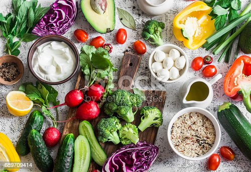 istock Balanced healthy diet food background in a Mediterranean style. Fresh vegetables, wild rice, fresh yogurt and goat cheese on a light background, top view. Flat lay 689709414