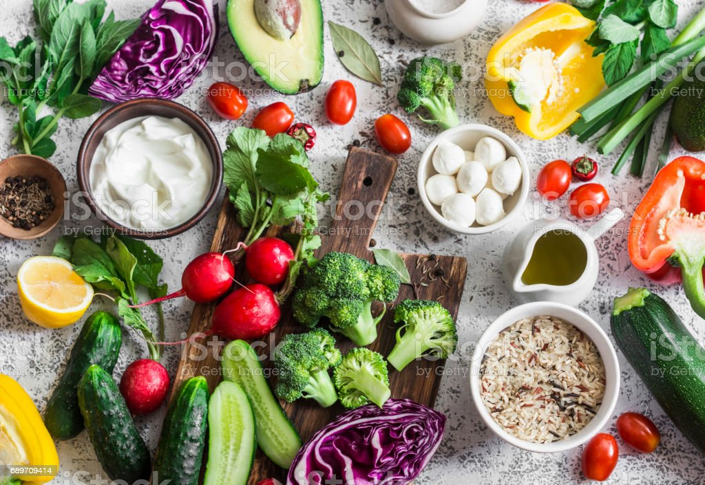 Balanced healthy diet food background in a Mediterranean style. Fresh vegetables, wild rice, fresh yogurt and goat cheese on a light background, top view. Flat lay stock photo