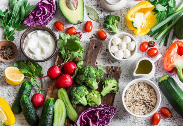 Ausgewogene gesunde Ernährung essen Hintergrund im mediterranen Stil. Frisches Gemüse, Wildreis, frischen Joghurt und Ziegenkäse auf einem hellen Hintergrund, Ansicht von oben. Flach zu legen – Foto