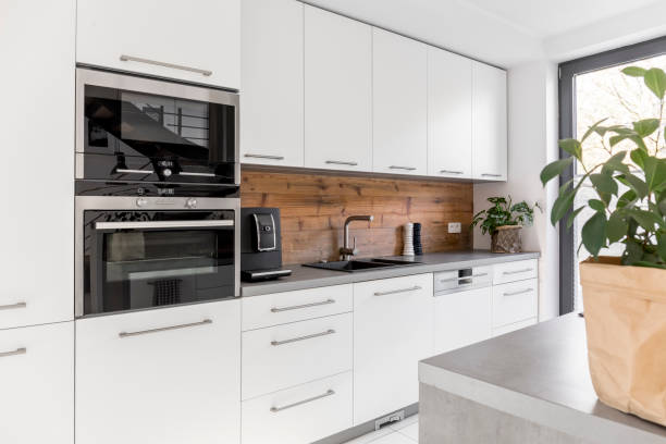 Balanced kitchen with natural accents Balanced kitchen with white cabinets grey worktop and natural accents symmetry stock pictures, royalty-free photos & images