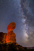 Iconic Balanced Rock illuminated against a star-filled Milky Way in Arches National Park in Moab, Utah.