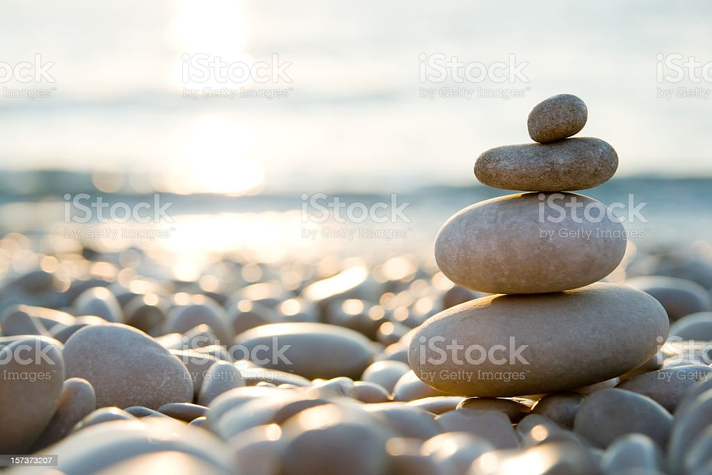 Balanced stones on a pebble beach during sunset.