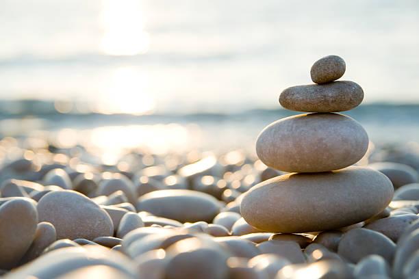 bei einem ausgewogenen steine kiesel strand bei sonnenuntergang. - gleichgewicht stock-fotos und bilder
