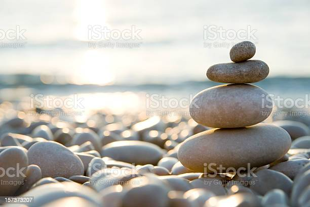 Photo of Balanced stones on a pebble beach during sunset.