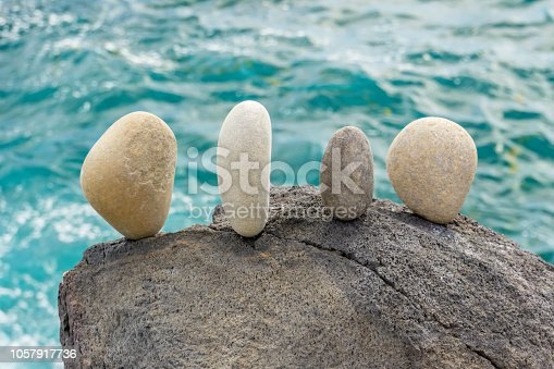 A small group of stones balanced on a rock at the waters edge