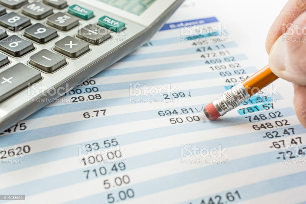 Balancing a bank statement close-up with pencil and calculator stock photo