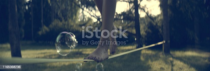 Young woman keeping balance on a slackline. Surrounded by floating bubbles
