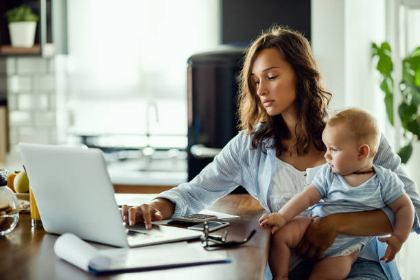 Balancing between motherhood and work! Young mother working on laptop while being at home with her baby son. between stock pictures, royalty-free photos & images